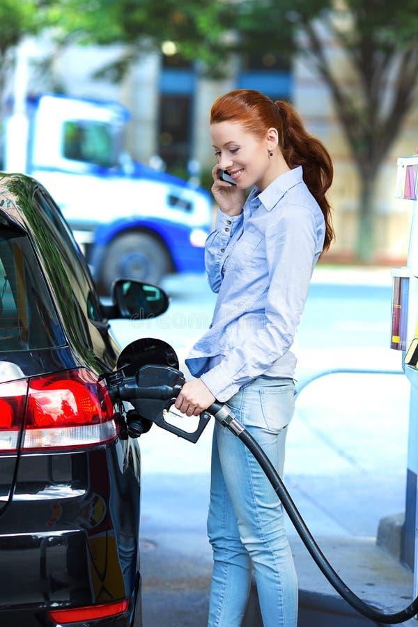 Attraktiv kvinna som tankar hennes bil på bensinstationen arkivbilder