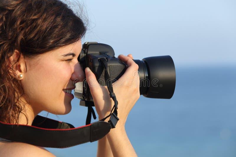 Attraktiv kvinna som tar ett fotografi med hennes kamera arkivbilder