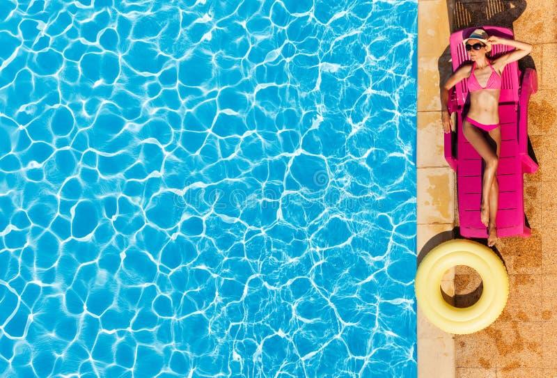 Attraktiv kvinna som tycker om solbränna av simbassängen royaltyfri bild