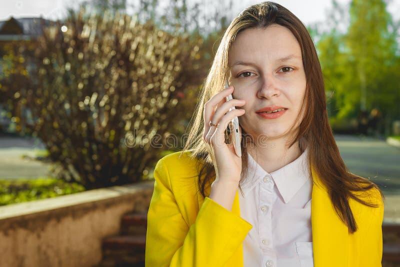 Attraktiv kvinna som utomhus använder mobiltelefonen royaltyfri foto