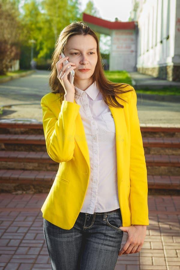 Attraktiv kvinna som utomhus använder mobiltelefonen arkivfoto