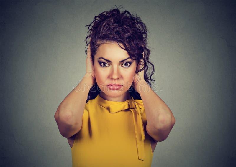 Attraktiv kvinnabeläggning med händer henne öron som ser kameran royaltyfri fotografi