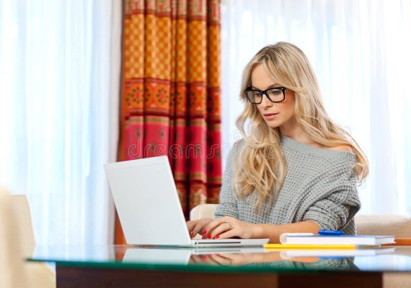 Attraktiv kvinnahandstil på bärbar dator arkivfoton