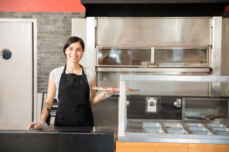 Attraktiv kvinnakock som visar stor smaklig pizza, medan stå beh royaltyfria bilder