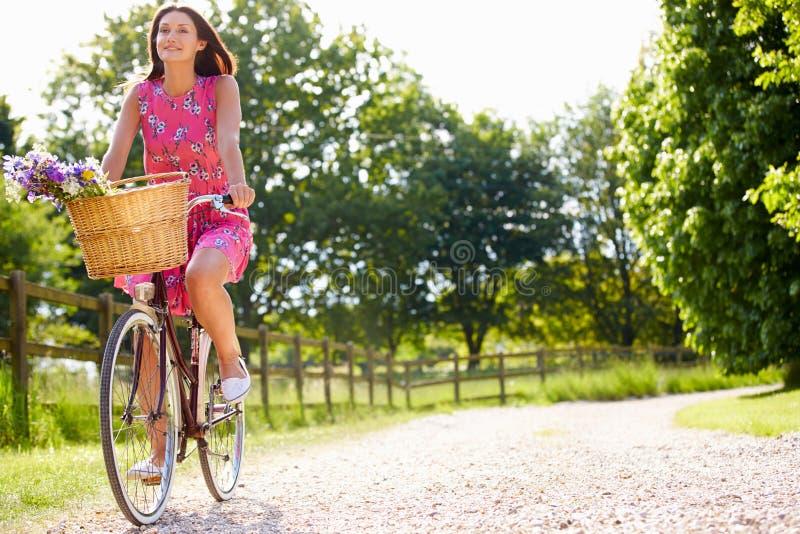 Attraktiv kvinnaridningcykel längs landsgränd fotografering för bildbyråer