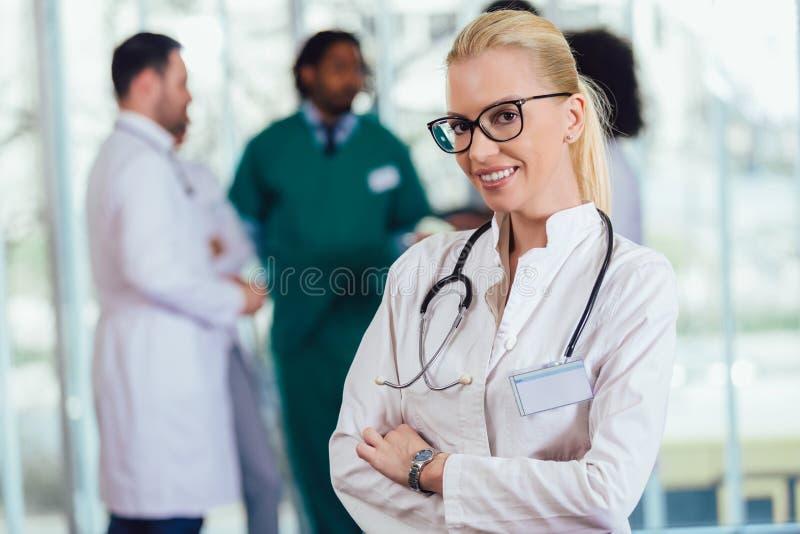 Attraktiv kvinnlig doktor på sjukhuskorridoren som ser att le för kamera fotografering för bildbyråer