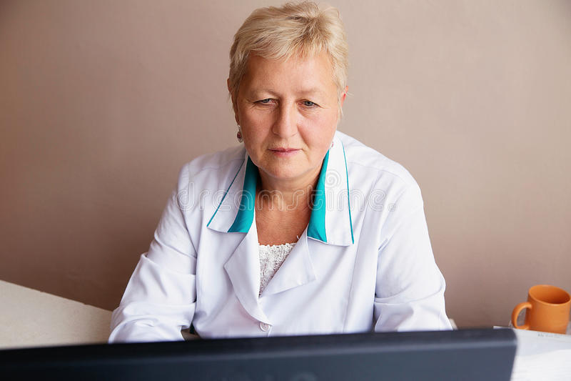 Attraktiv kvinnlig doktor som arbetar på hennes dator i hennes kontor arkivbild