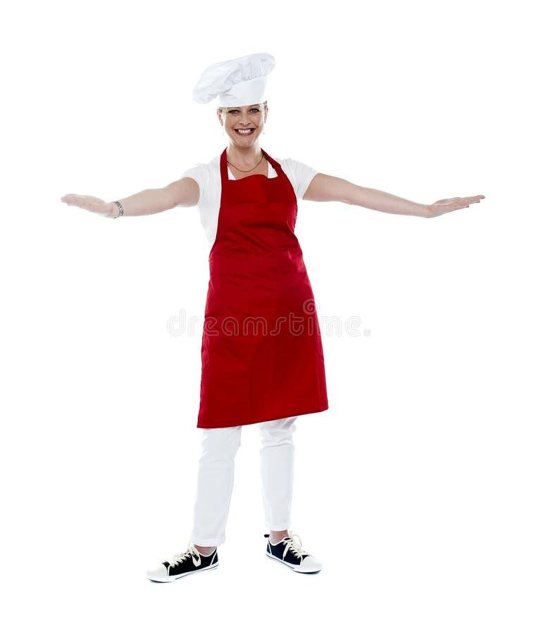 Attraktiv kvinnlig kock i rött förkläde och toque arkivbild