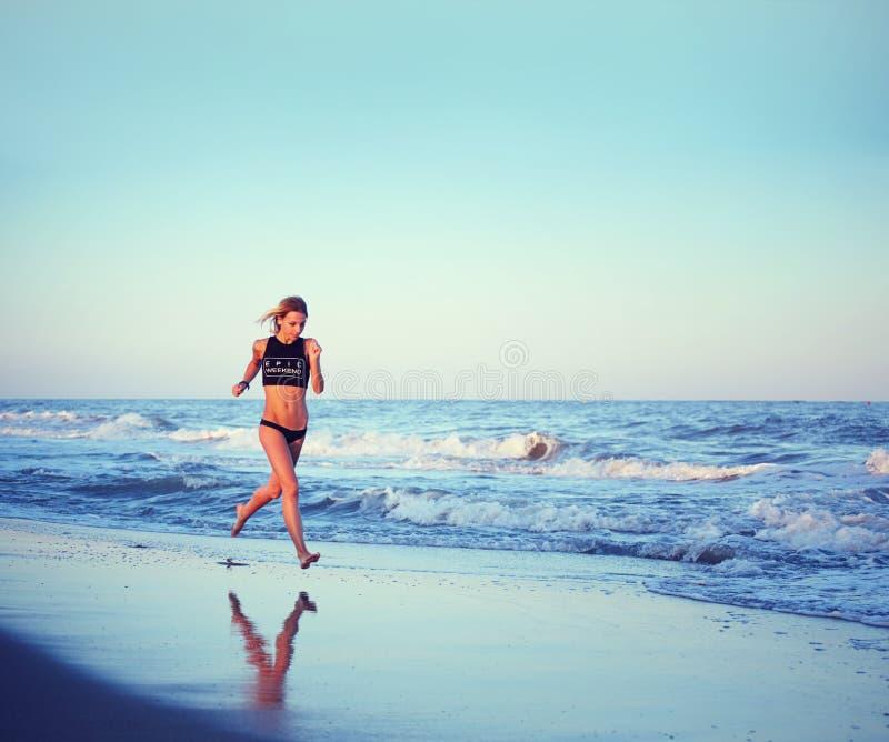 Attraktiv kvinnlig löparespring längs stranden på den fantastiska solnedgången med havet på bakgrund arkivfoton