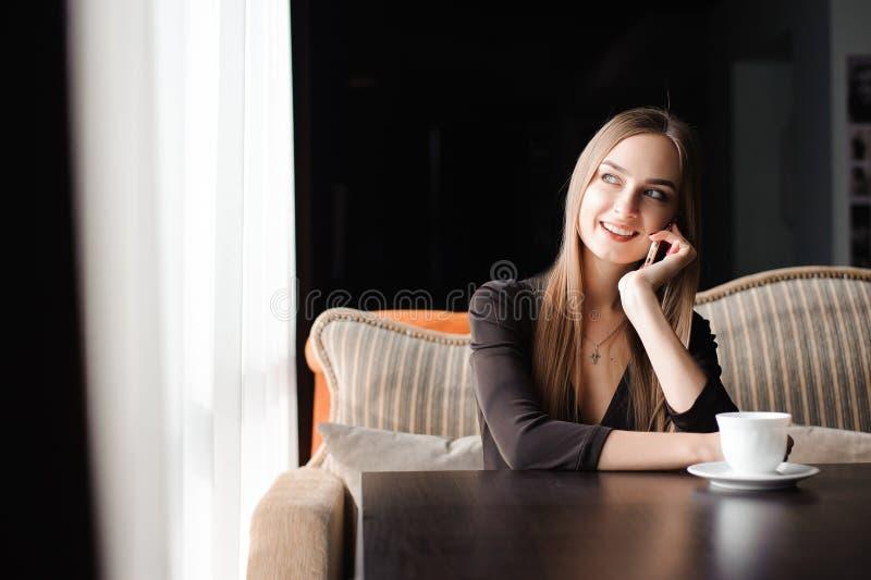 Attraktiv kvinnlig med det gulliga leendet som har talande konversation med mobiltelefonen, medan vila i kafé arkivbilder