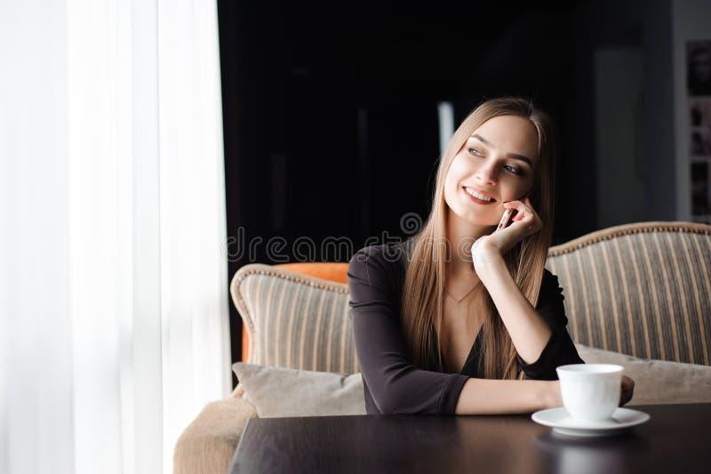 Attraktiv kvinnlig med det gulliga leendet som har talande konversation med mobiltelefonen, medan vila i kafé arkivfoton