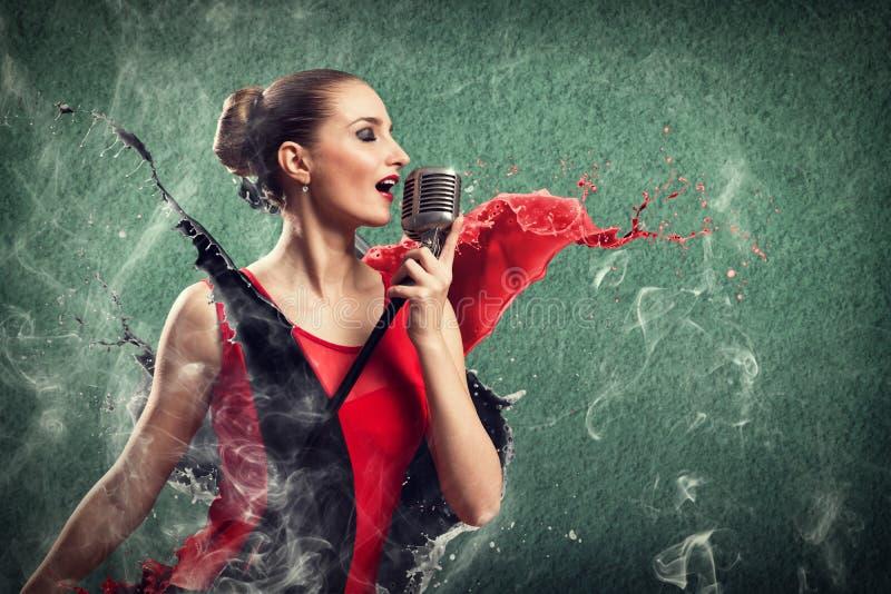 Attraktiv kvinnlig sångare med mikrofonen arkivbilder
