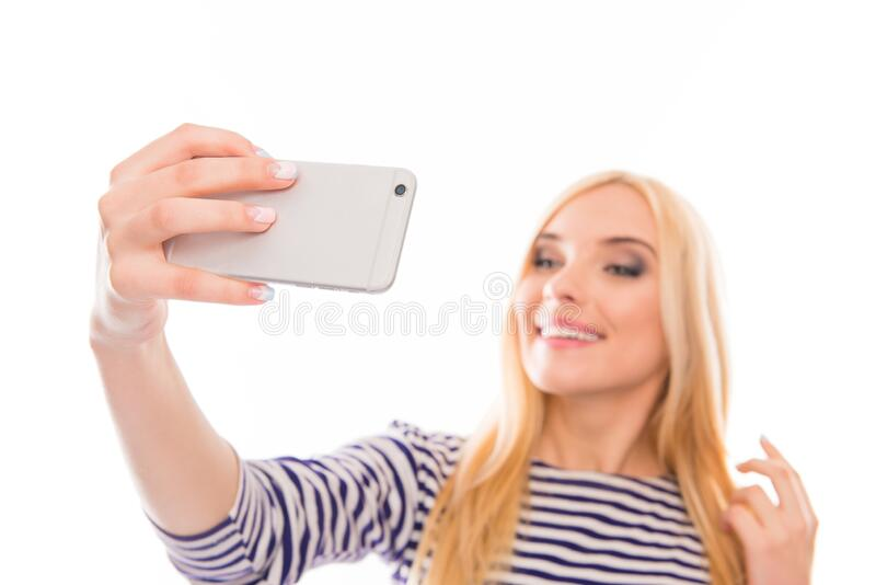 Attraktiv lächelnde Blondine, die sich auf ihrem Smartphone selbst macht stockfotografie