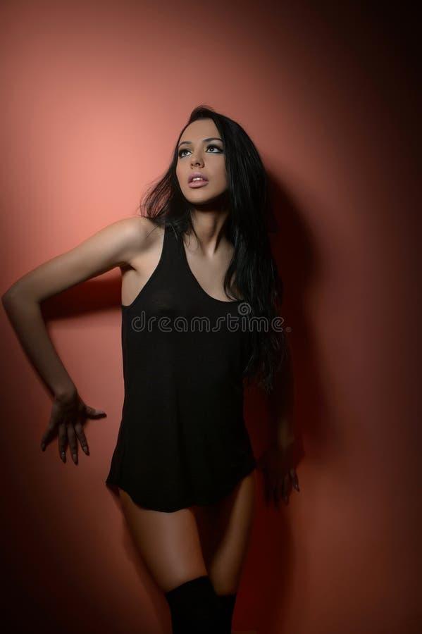Attraktiv lång modell för mörkt hår i svart T-skjorta och långa strumpor som står på tegelsten-röd bakgrund sinnlig kvinna för st royaltyfri bild