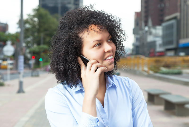 Attraktiv latinamerikansk kvinna i staden på telefonen royaltyfri bild