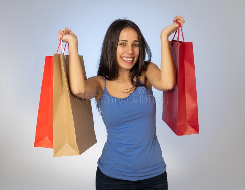 Attraktiv latinsk ung tonåring med shoppingpåsar som känner sig för att overjoy, och lycka arkivfoto
