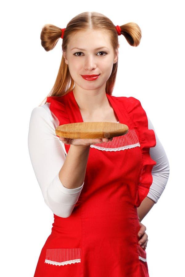 Attraktiv le hemmafru i rött förkläde med roliga hästsvansar a fotografering för bildbyråer