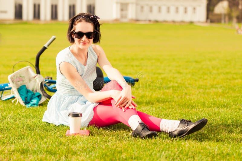 Attraktiv le hipsterkvinna i tillfällig kläder som står på G royaltyfria bilder