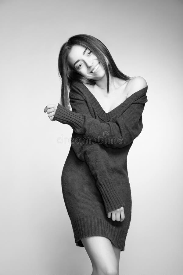 Attraktiv le kvinna med långt hår på grå färger royaltyfri foto