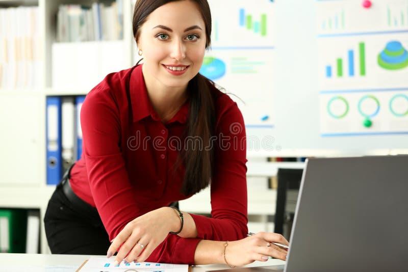 Attraktiv le kvinnlig arbetare som bär den röda blusen arkivfoto