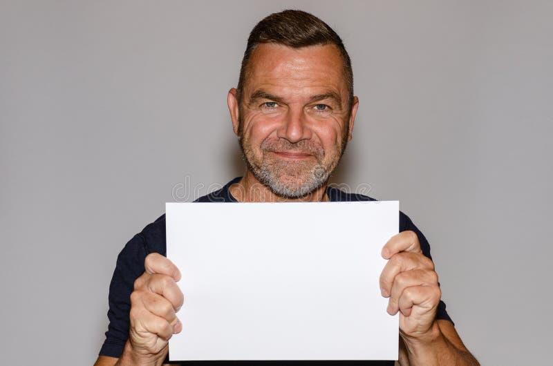 Attraktiv le medelålders man som rymmer ett tecken arkivfoton