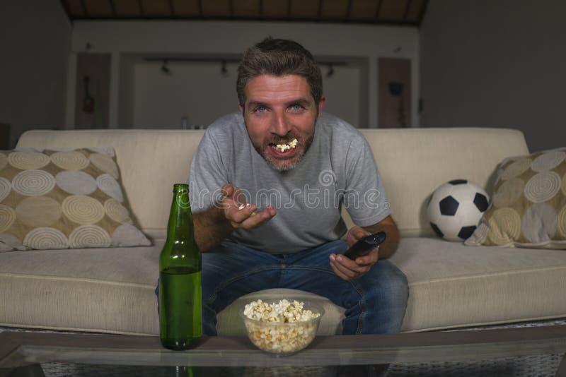 Attraktiv lek för fotboll för nervös och upphetsad fotbollsupporterman hållande ögonen på på den hemmastadda soffasoffan för tele royaltyfri foto