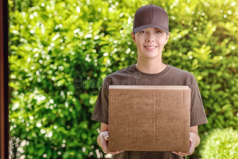 Attraktiv leveranskvinna med en kartong royaltyfria foton