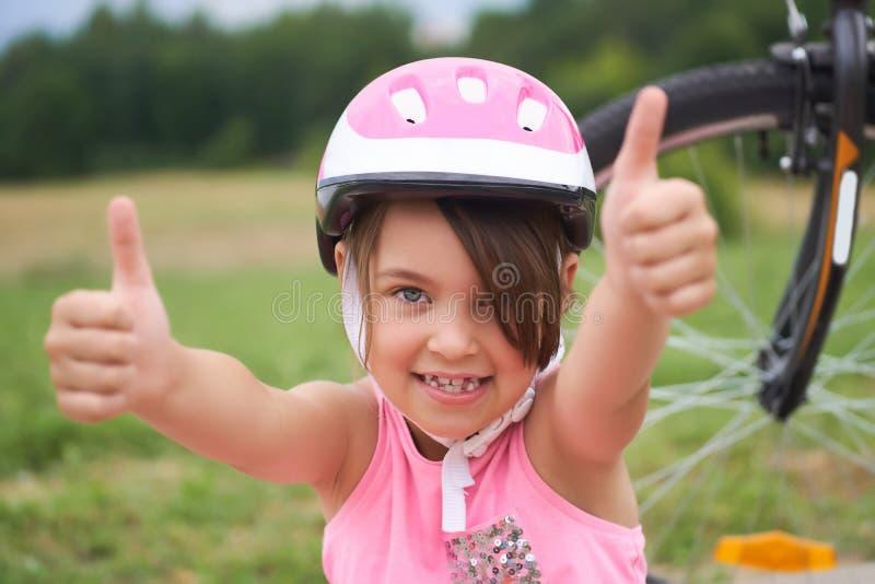 Attraktiv liten cyklist som ger upp tummar Lycklig glad liten flicka med cykeln på bakgrunden som gör en gest upp tummen royaltyfria bilder