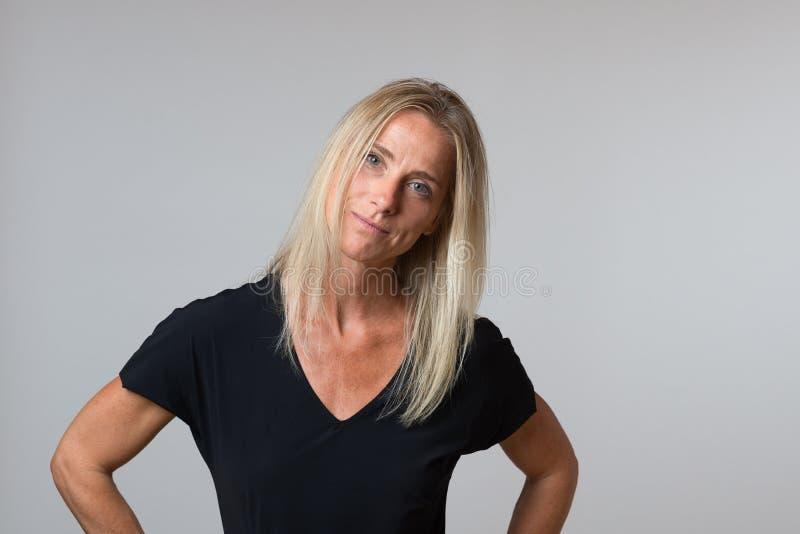Attraktiv lycklig blond kvinna med ett tyst leende arkivfoto