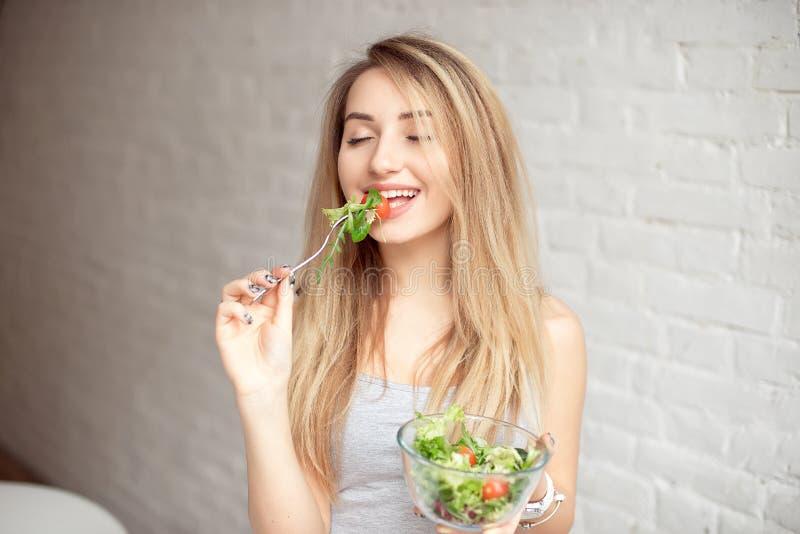 Attraktiv lycklig kvinnainnehavbunke av sallad för ny grönsak i händer som äter med gaffeln, enjoing sund mat fotografering för bildbyråer