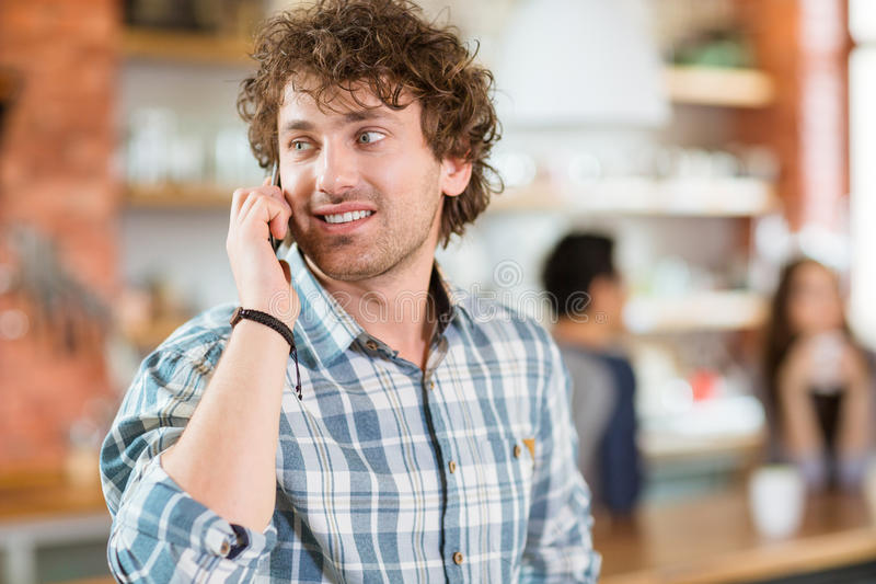 Attraktiv lycklig modern ung lockig man som talar på mobiltelefonen arkivfoton