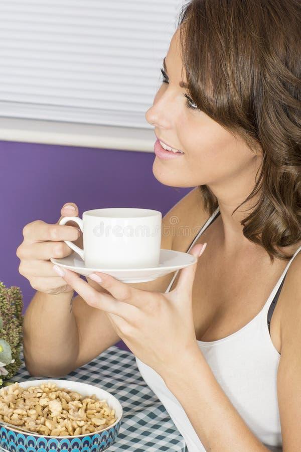 Attraktiv lycklig sund säker avkopplad ung kvinna som har frukosten som dricker kaffe fotografering för bildbyråer