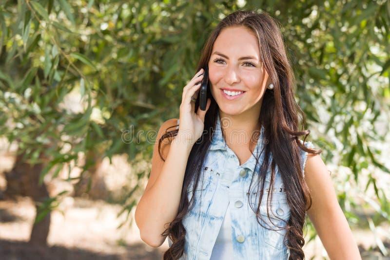 Attraktiv lycklig tonårig kvinnlig för blandat lopp som talar på mobiltelefonnolla arkivfoto