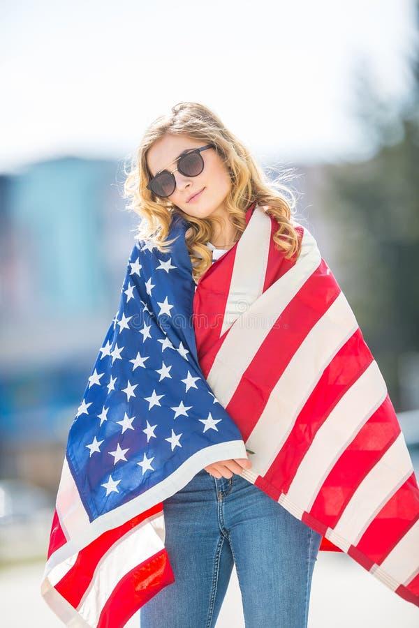 Attraktiv lycklig ung flicka med flaggan av USAen arkivfoto