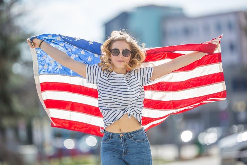 Attraktiv lycklig ung flicka med flaggan av USAen fotografering för bildbyråer
