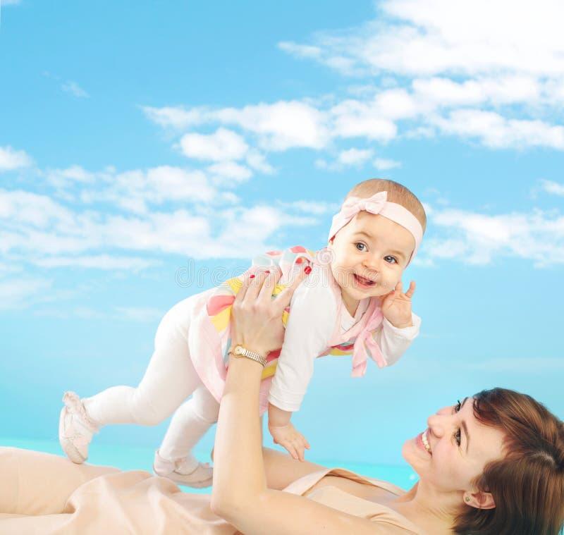 Attraktiv mamma som rymmer hennes mycket lilla dotter royaltyfri foto