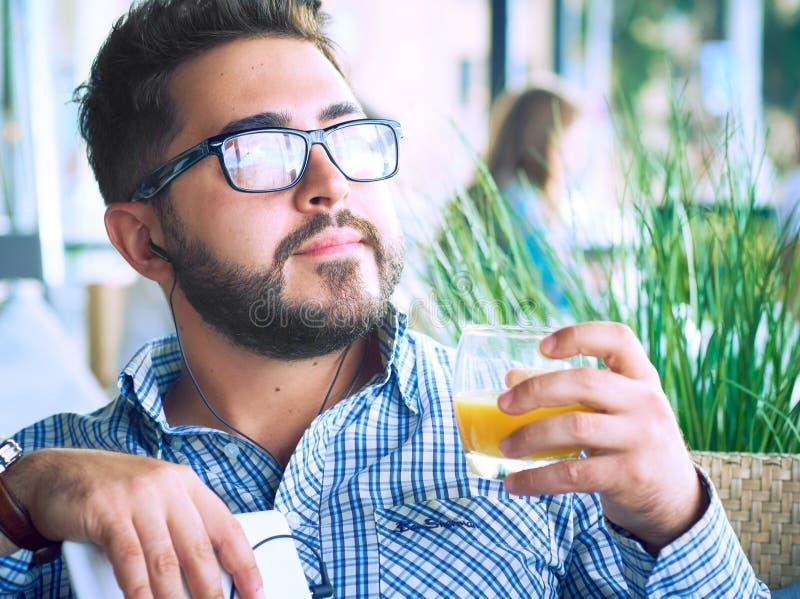 Attraktiv man för arabisk egyptisk ung affär som har ett kaffeavbrott och dricker orange fruktsaft i kafé fotografering för bildbyråer
