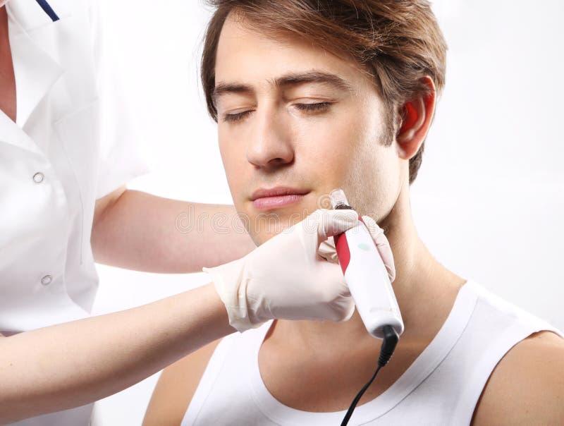 Attraktiv man i en skönhetsalong, mesotherapy behandling för mikrovisare arkivbilder