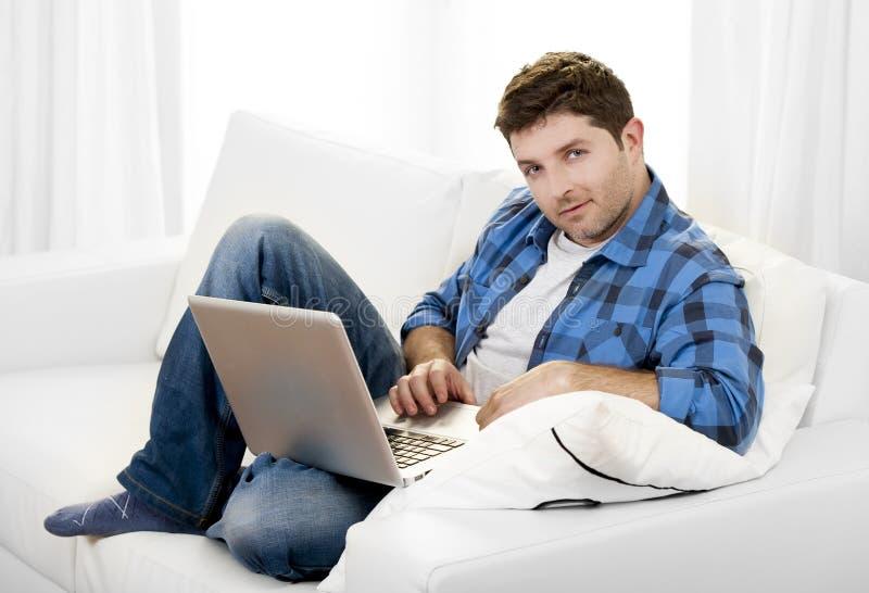 Attraktiv man med datorsammanträde på soffan fotografering för bildbyråer