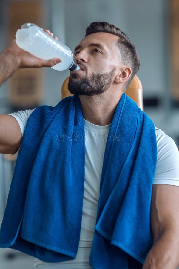 Attraktiv man som dricker buteljerat vatten i idrottshallen arkivbild
