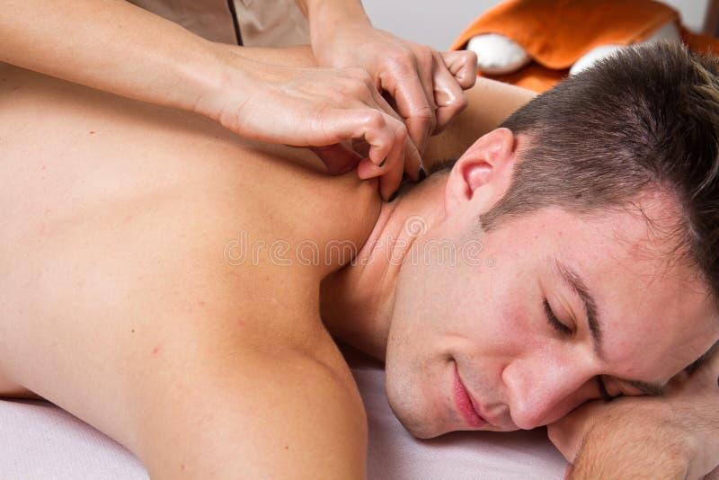 Attraktiv man som har en tillbaka massage arkivbilder