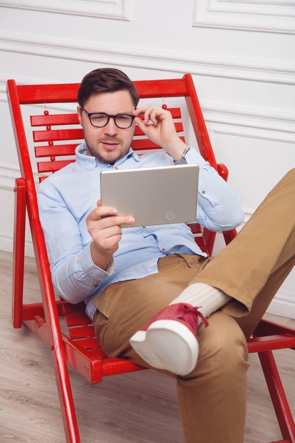 Attraktiv man som hemma arbetar på minnestavlaPC arkivfoto