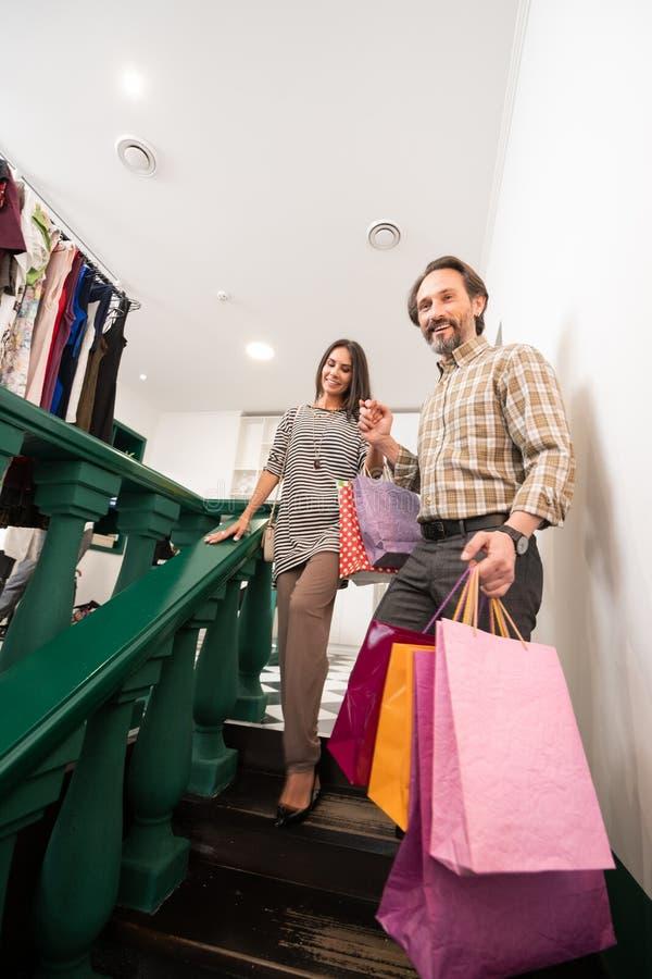 Attraktiv man som hjälper denseende damen med shoppingpåsar royaltyfria bilder
