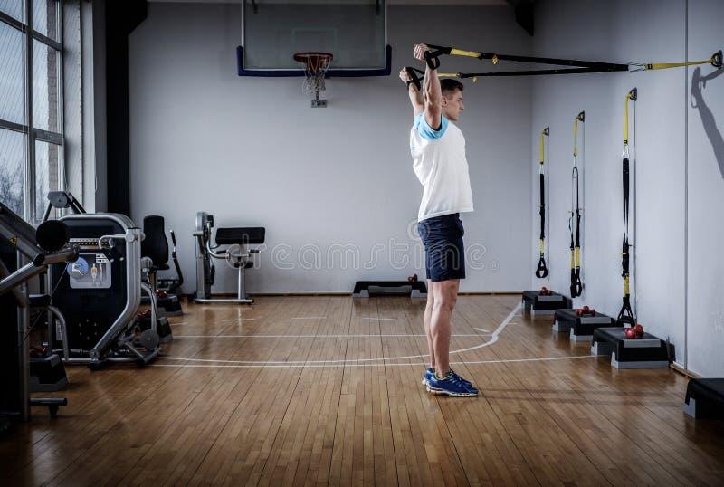 Attraktiv man under genomkörare med upphängningremmar i idrottshallen arkivfoto