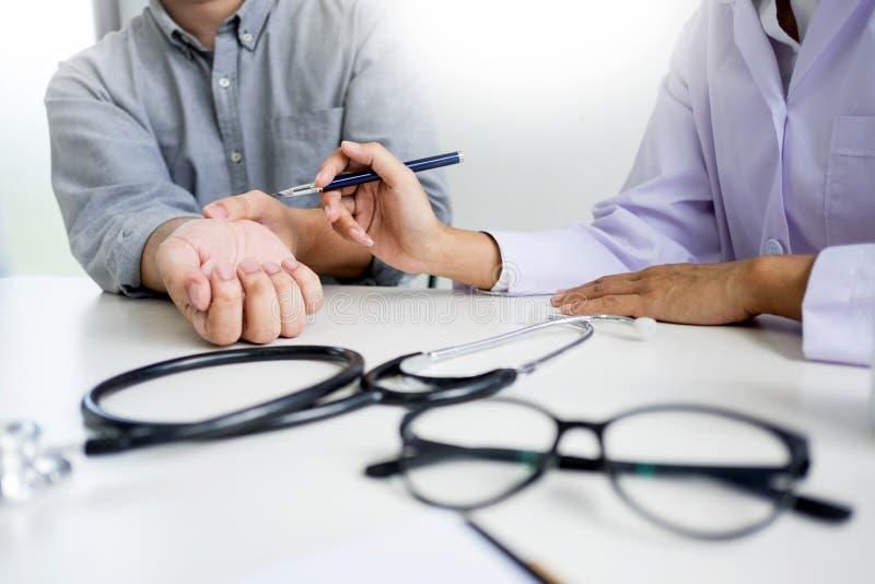 Attraktiv manlig doktor Examining som diskuterar rapporter med tålmodigt lidande för massage från tillbaka, smärtar i klinik royaltyfri foto