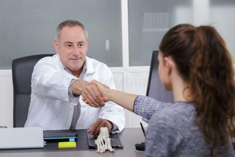 Attraktiv manlig doktor som i regeringsställning skakar patienthänder royaltyfria bilder