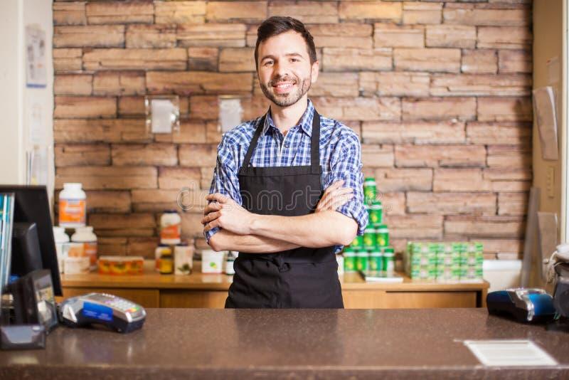 Attraktiv manlig kassörska i en livsmedelsbutik royaltyfria foton