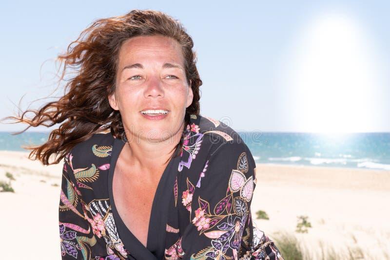 Attraktiv medelålders brunettkvinna på sjösidasommaren fotografering för bildbyråer