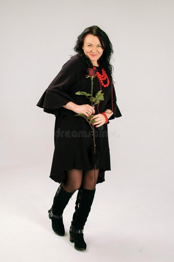 Attraktiv medelålders kvinna med röda Rose Dancing i studio i svart klänning och person som tillhör en etnisk minoritethalsband arkivbilder