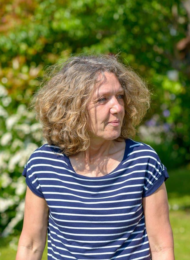 Attraktiv medelålders kvinna som går i en trädgård royaltyfria bilder